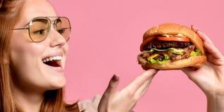 Sluit omhoog portret van een hongerige jonge vrouw die hamburger over roze achtergrond eten stock fotografie