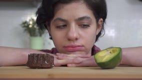 Sluit omhoog portret van een jong peinzend meisje die een moeilijk besluit nemen Het meisje kiest tussen sappige avocado en a stock video