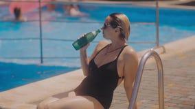 Sluit omhoog portret van een jong vrouwen drinkwater na oefenings openlucht dichtbijgelegen zwembad stock footage