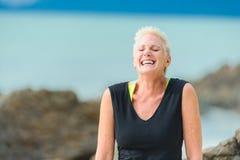 Sluit omhoog portret van een lachende rijpe oude vrouw op een woestijn RT stock fotografie