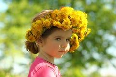 Sluit omhoog portret van een leuk twee jaar oud meisje die een paardebloemkroon, blik over schouder dragen Stock Afbeelding