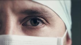 Sluit omhoog portret van een een mens chirurg of arts met masker klaar voor verrichting in het ziekenhuis of kliniek stock videobeelden