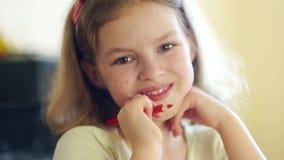 Sluit omhoog portret van een mooi krullend meisje Een schoolmeisje bekijkt de camera en glimlacht Het meisje heeft binnen een roo stock video