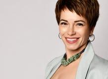 Sluit omhoog portret van een professionele korte haar bedrijfsvrouw die op grijs glimlachen royalty-vrije stock foto's