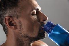 Sluit omhoog portret van een rijp shirtless sportman drinkwater Stock Foto