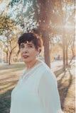 Sluit omhoog portret van een Spaanse hogere vrouw in het park bij zonsondergang stock fotografie