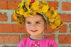 Sluit omhoog portret van een twee jaar oud meisje die een paardebloemkroon dragen Stock Foto's