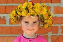 Sluit omhoog portret van een twee jaar oud meisje die een paardebloemkroon dragen Royalty-vrije Stock Afbeeldingen