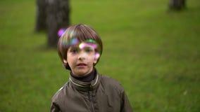 Sluit omhoog portret van een zeer leuke jonge jongen die zeepbels vangt Slow-motion stock video