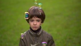 Sluit omhoog portret van een zeer leuke jonge jongen die zeepbels vangt Slow-motion stock videobeelden