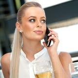 Het vrouwelijke uitvoerende spreken op slimme telefoon bij restaurant. Stock Afbeeldingen