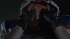 Sluit omhoog portret van gebaarde Amerikaanse voetbalster die in handschoenen op een hitte zijn hoofd zetten, vooruit kijkend met stock footage