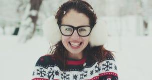 Sluit omhoog portret van gelukkig meisje met oormoffen, in ijzig de winterpark Vliegende sneeuwvlokken Glimlachend aan blije came stock footage