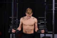 Sluit omhoog portret van geschikte jonge mens het opheffen gewichten in gymnastiek op donkere achtergrond Stock Fotografie