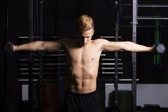 Sluit omhoog portret van geschikte jonge mens het opheffen gewichten in gymnastiek op donkere achtergrond Royalty-vrije Stock Foto