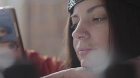 Sluit omhoog portret van getatoeeerd hipster meisje die een bericht in smartphone typen en op de achtergrond van de workshop geeu stock footage