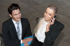 Gelukkige onderneemster met slimme telefoon en partner. Stock Foto's
