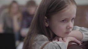Sluit omhoog portret van het kleine droevige meisje met lange haarzitting op de stoel in de voorgrond De bezige moeder en stock footage