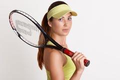 Sluit omhoog portret van het mooie energieke sterke tennisspeler bekijken direct camera, houdend tennisracket in één hand, royalty-vrije stock afbeeldingen