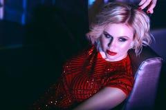 Sluit omhoog portret van het mooie glam blonde model ontspannen op de bank in nachtclub in kleurrijke neonlichten stock foto