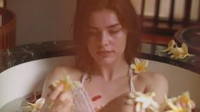 Sluit omhoog portret van het mooie sexy jonge vrouwelijke ontspannen in de ton van het bloemenbad stock footage