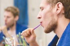 Sluit omhoog portret van jonge gebaarde mensen schone tanden met tandenborstel voor spiegel royalty-vrije stock foto