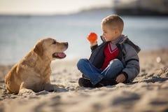 Sluit omhoog portret van jonge jongen het spelen bal met zijn hond op het strand Stock Afbeeldingen