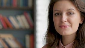 Sluit omhoog portret van jonge mooie bibliothecarisvrouw die het gelukkige bekijken camera op de achtergrond van het bibliotheekb stock videobeelden