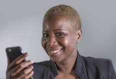 Sluit omhoog portret van jonge mooie en gelukkige in zwarte afro Amerikaanse vrouw die en mobiele die telefoon houden met behulp  stock foto