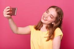 Sluit omhoog portret van jonge mooie modieuze vrouwen die selfie, gebruikend haar eigen smartphone, glimlachen bij camera, gekled stock foto's