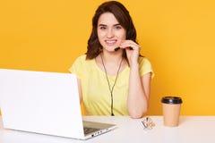 Sluit omhoog portret van jonge onderneemster in hoofdtelefoons met microfoon voor geopende laptop, zit bij witte lijst, heeft Cu  stock afbeeldingen