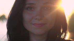 Sluit omhoog portret van jonge vrij donkerbruine vrouw op een zonsondergangachtergrond op een meer stock footage