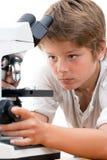 Sluit omhoog portret van jongen met microscoop. stock afbeelding