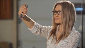 Sluit omhoog portret van leuk meisje met krullende smartphone van de haarholding stock footage