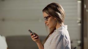 Sluit omhoog portret van leuk meisje met krullende smartphone van de haarholding stock video