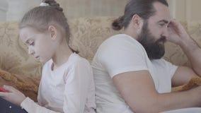 Sluit omhoog portret van leuke dochter en haar vaderzitting op de bank op woonkamer met cel telefoons en binnen het koelen stock footage