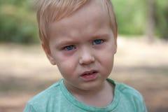 Sluit omhoog portret van leuke Kaukasische babyjongen met ernstige uitdrukking in blauwe ogen stock afbeelding