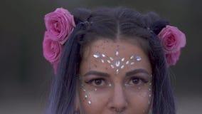 Sluit omhoog portret van leuke sensuele jonge vrouw met mooie ogen van de schitterings de make-up doordrongen neus en een bloemka stock videobeelden
