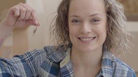 Sluit omhoog portret van leuke vrouw in geruit overhemd die sleutel van huis kijken tonen in camera met brede glimlach positief stock footage