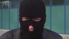 Sluit omhoog portret van misdadige mensendief of rover die in masker camera bekijken stock footage