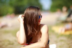 Sluit omhoog portret van modieuze mooie sexy vrouw in glazen en met nat haar op een zonnig strand met blauw water stock fotografie