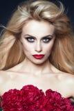 Sluit omhoog portret van mooi model met blond haar die in de wind blazen en perfectioneer omhoog maken Bos van pioenen die haar b stock foto
