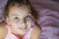 Sluit omhoog portret van mooi tienermeisje die in roze kleding enthousiast met een glimlach de camera bekijken Stock Afbeelding