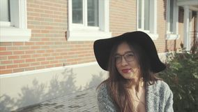 Sluit omhoog portret van mooie glimlachende vrouw in zwarte hoed en glazen openlucht stock footage