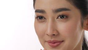 Sluit omhoog portret van mooie jonge Aziatische vrouw wat betreft gezicht en gezonde huid in langzaam motie skincare concept stock videobeelden