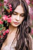 Sluit omhoog portret van mooie jonge donkerbruine vrouw die in openlucht naast Sakura, neer kijken royalty-vrije stock afbeeldingen