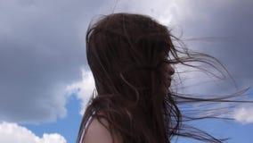 Sluit omhoog portret van mooie jonge vrouw met blazend haar in wind stock footage