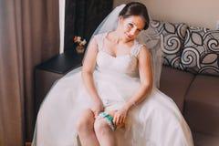 Sluit omhoog portret van mooie Kaukasische medio volwassen bruid die haar kouseband kleden Stock Afbeeldingen