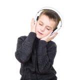Sluit omhoog portret van ogen het gesloten jongen luisteren aan muziek met hea royalty-vrije stock afbeelding
