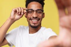 Sluit omhoog portret van opgewekte vrolijke blij met toothy glimlach gekleed in witte t-shirt op gele achtergrond stock foto's